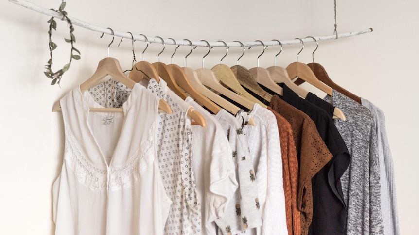 Different types of mostly female style blouses hang on floating rack.