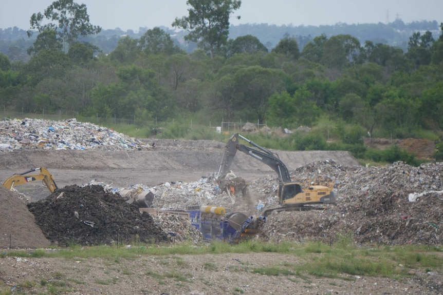 Two heavy loaders move construction waste at a landfill at New Chum, Ipswich