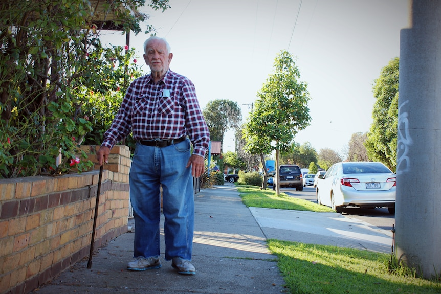 An elderly man with jeans and a checked shirt stands on a suburban street next to a brick fence.