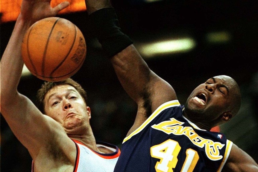 Lakers player Glen Rice and Phoenix player Luc Longley battle for basketball