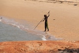 A boy uses a spear to fish at the beach in Maningrida, in the Gulf of Carpentaria.