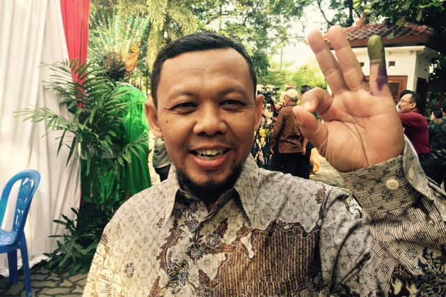 An Indonesian man shows off his ink-stained finger after voting in elections for Jakarta's next Governor