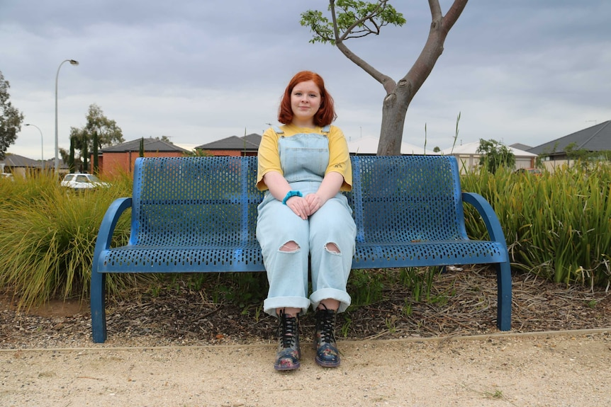 A young girl in overalls sitting on a park bench outside