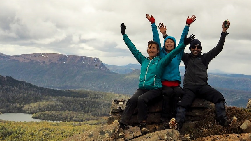 Mel and her friends wave their hands in the air, posing at a scenic lookout in the Tasmanian bush.