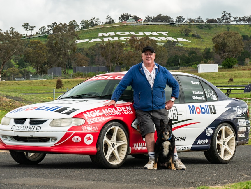 Keith Tucker standing in front of replica Holden racing car in front of Mount Panorama sign on hill.