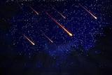 Glowing orange meteors in the sky.