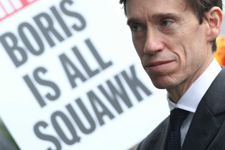 A close up of Rory Stewart with a sign in the background reading 'Boris is all squawk'.