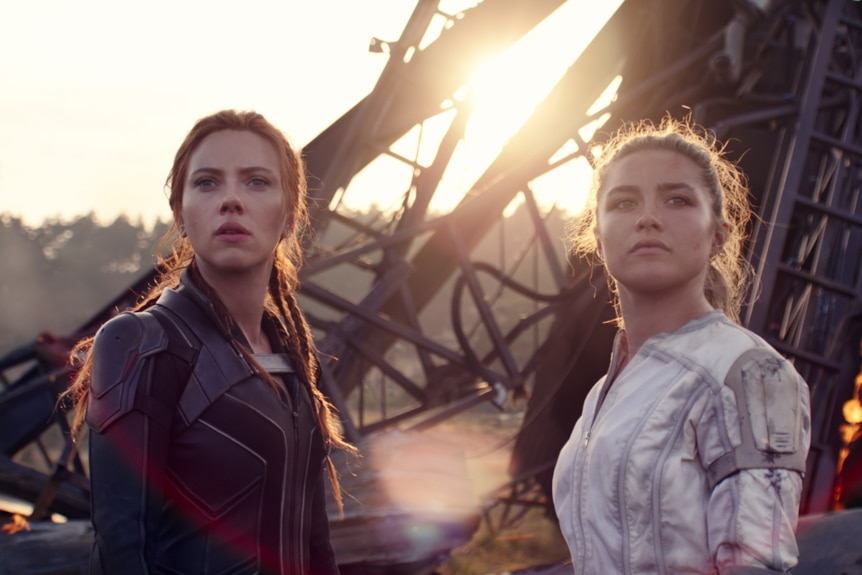 Scarlett Johansson and Florence Pugh stand in front of a pile of rubble, with determined expressions
