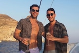 Daniel and Mike Christidis hugging and laughing on a boat while holding wine glasses.