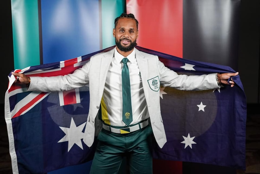An man wearing a beige suit jacket and green pants with a green tie holds the Australia flag