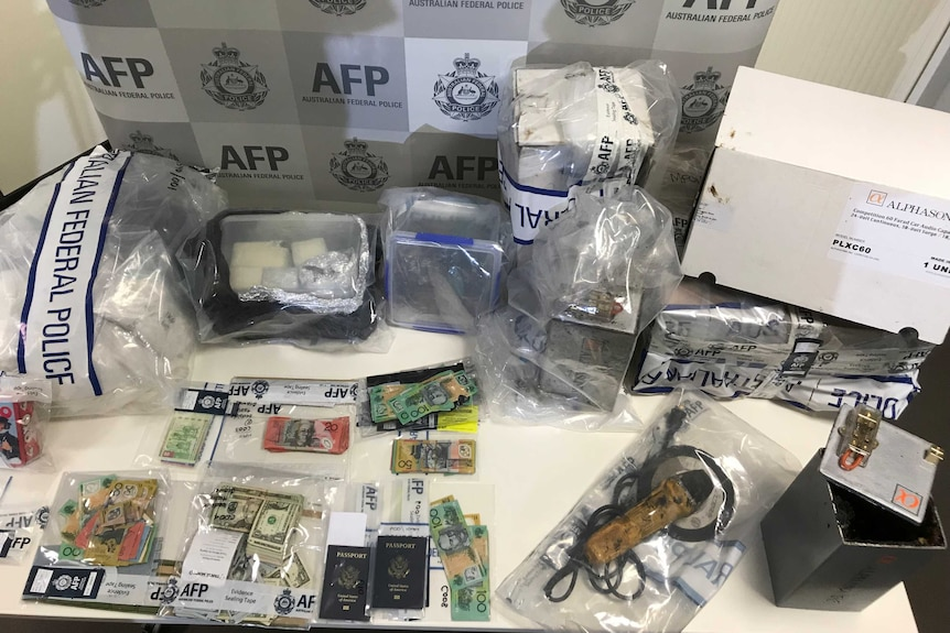A table with federal police evidence bags containing Australian and US dollars, passports, and other parcels.