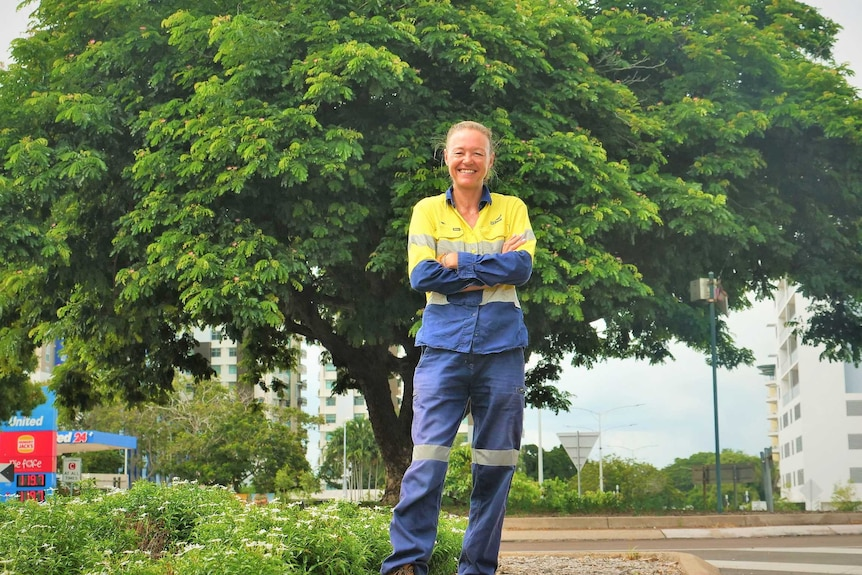 Woman in hi-viz workwear arms crossed on median strip with lush tree behind.