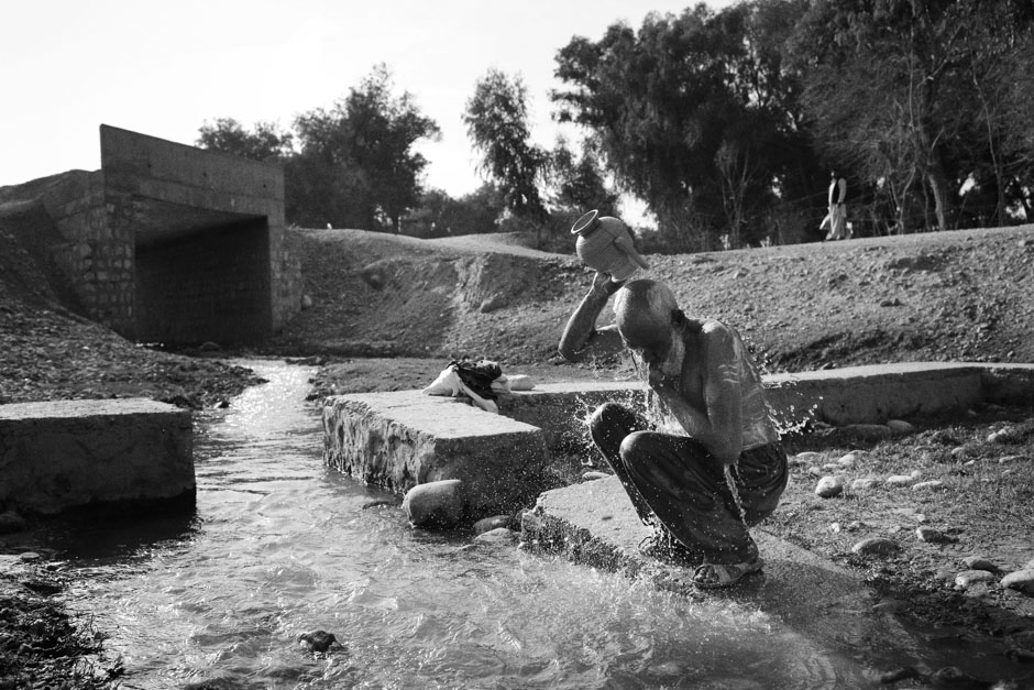 Haji Hazrat, originally from Afghanistan's Nangarhar Province, bathes himself in a canal outside Jalalabad
