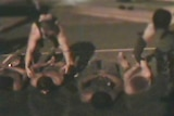 Four boys handcuffed and lying topless on the ground at night as two guards stand over them.
