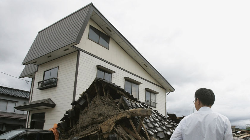 A man looks on at a collapsed house in northern Japan after an earthquake.