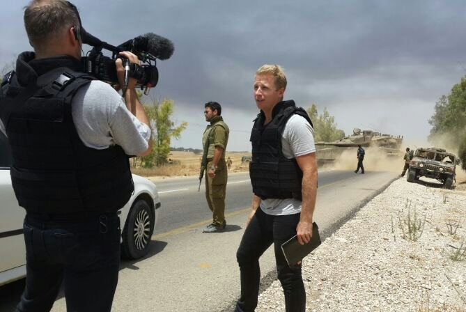 Macdonald wearing safety vest talking to camera with tanks and solders in background, location unknown.