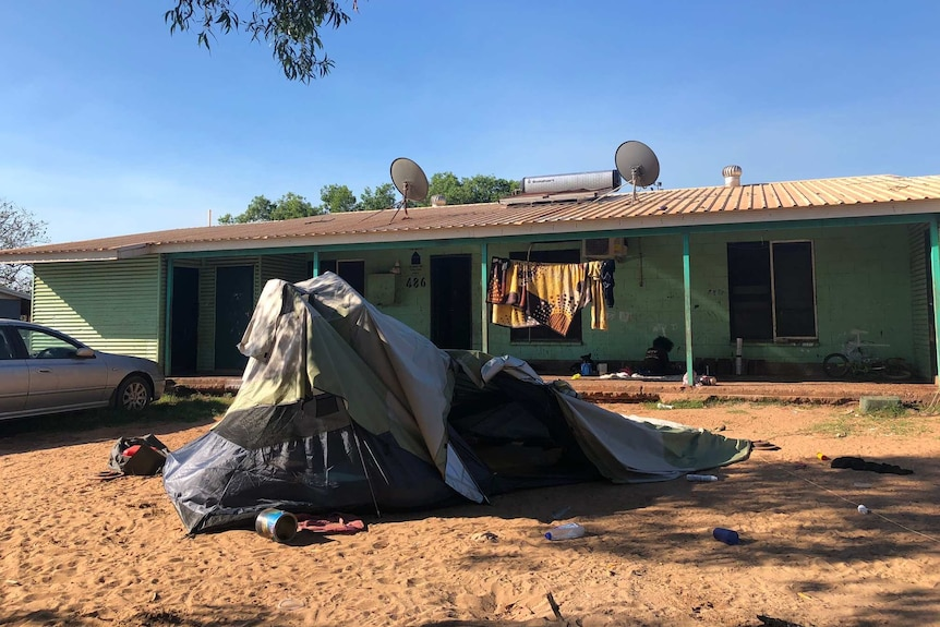 A green house with a collapsing tent in the front yard