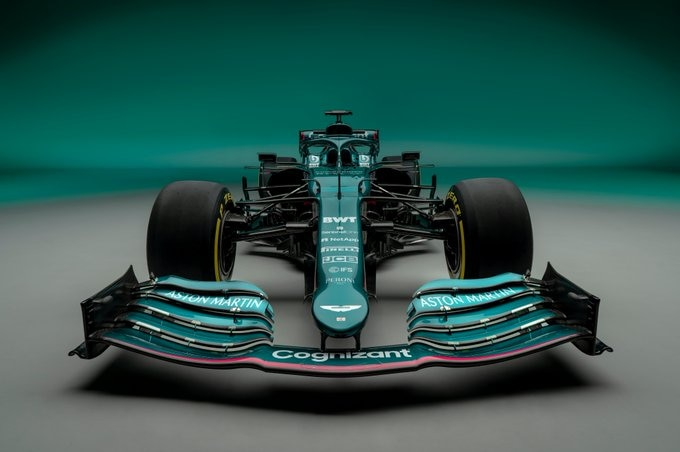 A driver-less Formula 1 car sits facing the camera in front of a metallic green background.