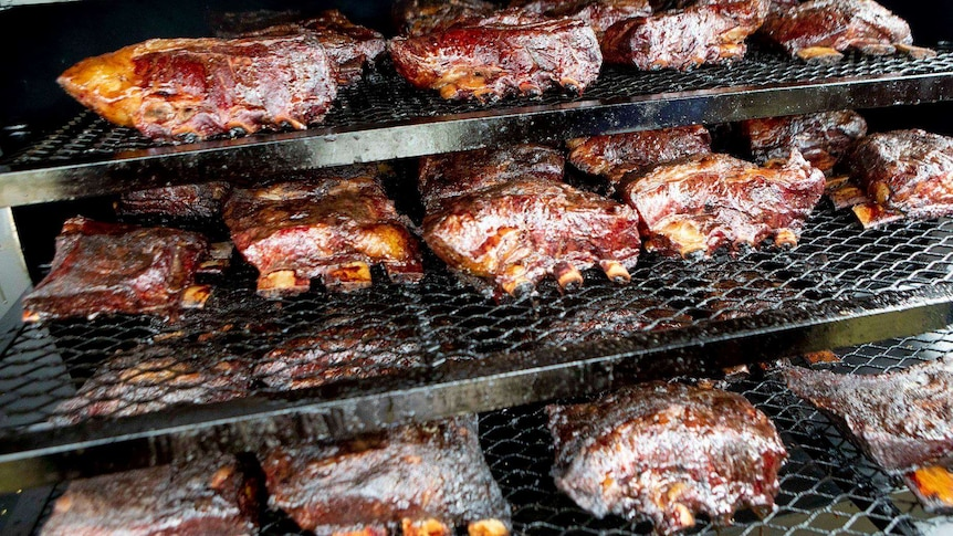 Beef ribs cooking on multiple grills.