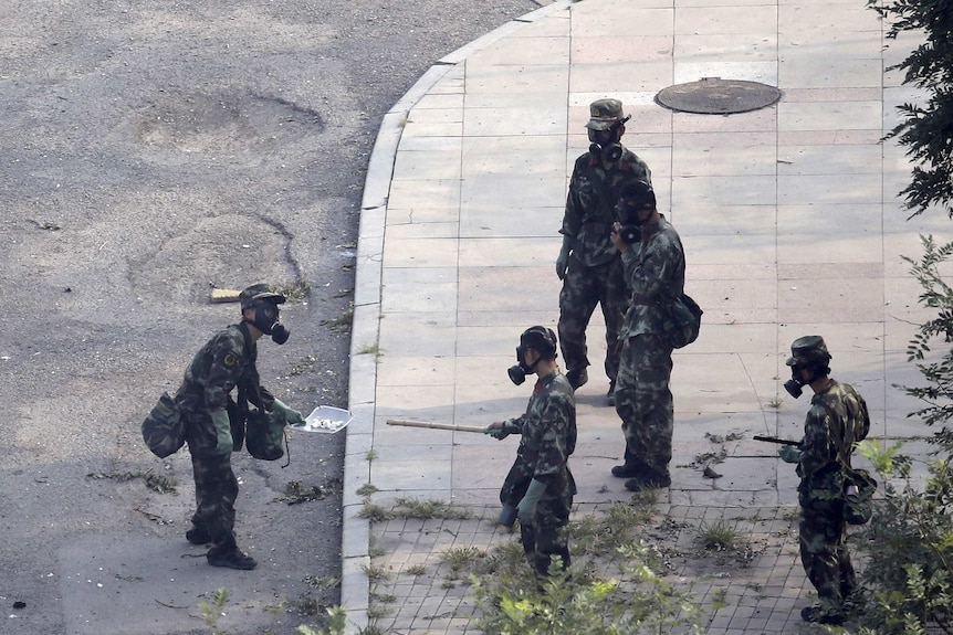 Chinese paramilitary police in gas mask examine chemicals at Tianjin blast site