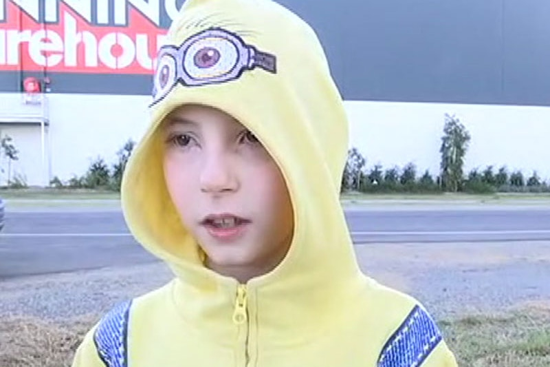 Nine-year-old student Philip Hale, dressed in a yellow minion hoodie, speaks to the ABC in a street.