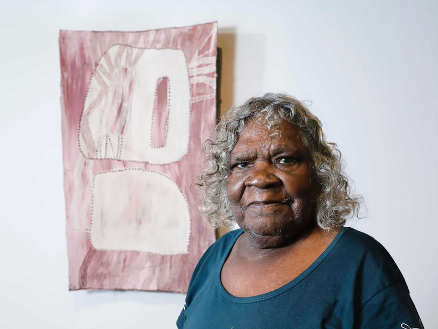 Interior, gallery. Woman with short curly grey hair standing in front of bark painting in pink and white tones.