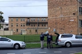 Three police officers gather outside brick flats in Ascot Vale during a police counter-terrorism operation.