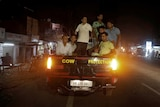 """A group of men piled into the bed of a pickup truck labelled """"cow protection""""."""