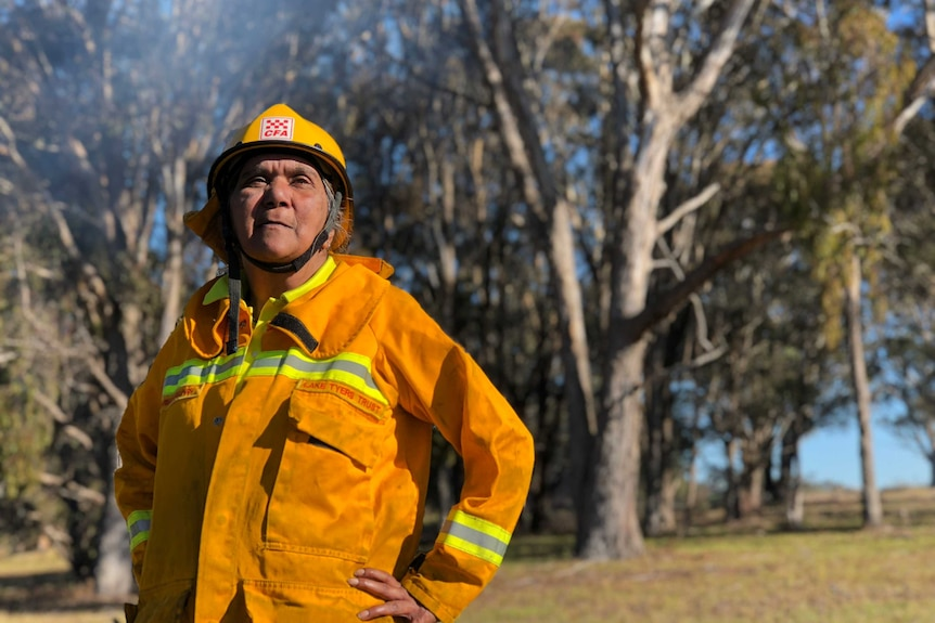 Charmaine Sellings wearing her yellow fire jacket with smoke and bush in the background.