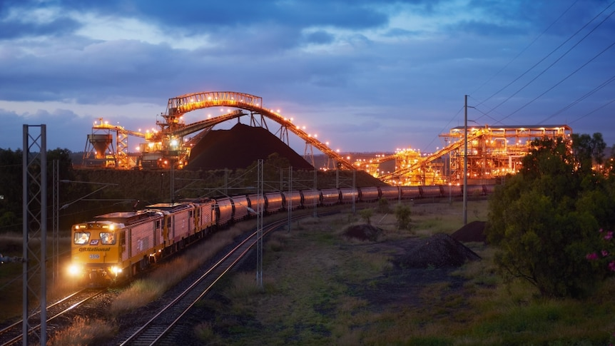 Long train with many carriages snakes its way along a track from a well-lit coal-loading facility at night