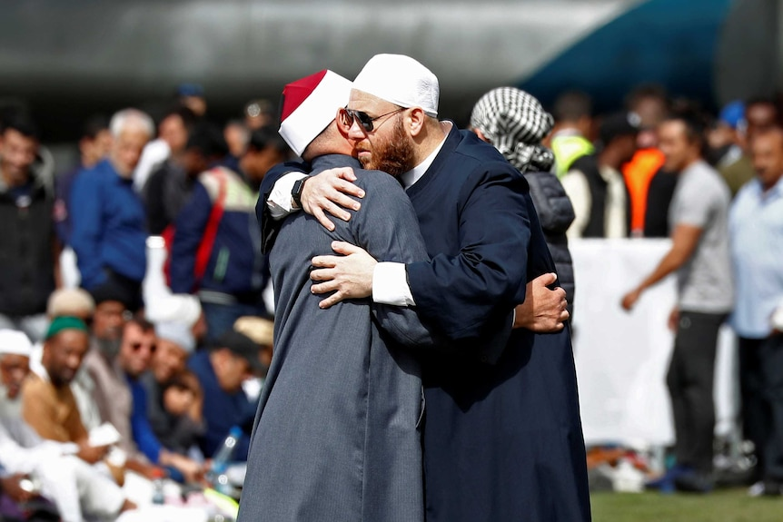 Two men hug at a memorial gathering after the Christchurch mosque attack.