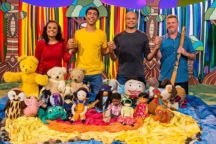 Miranda Tapsell, Hunter Page-Lochard, Luke Carroll and Matthew Doyle holding hands while standing behind the Play School toys