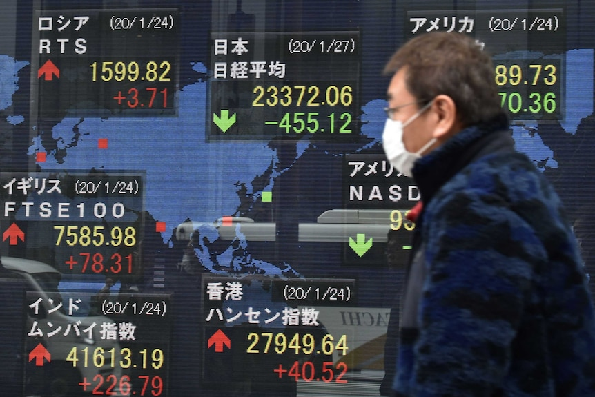 A man in a face mask walks past a stock market sign.