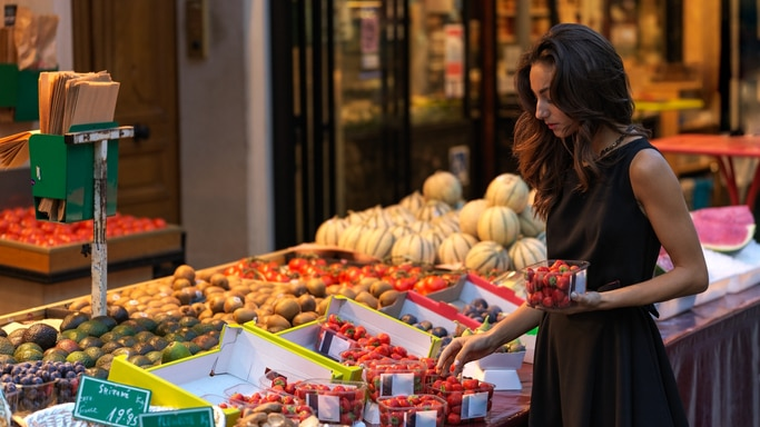 A woman buying fruit from a fruit stand.