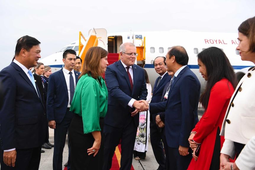 Australian Prime Minister Scott Morrison shakes hands with an official in Vietnam.