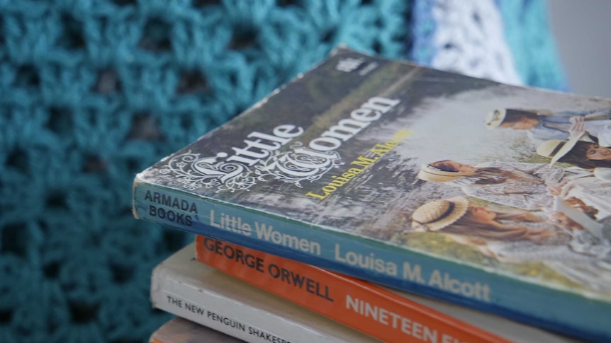 A stack of books - Little Women, Nineteen Eighty-four, Twelth Night sit on a blue crochet blanket