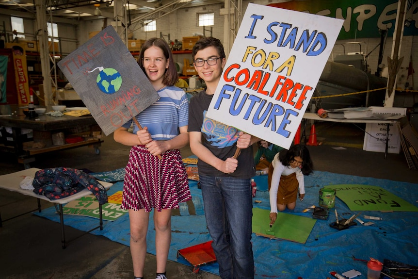 Two young people holding up placards: one reads, 'I stand for a coal free future' and the other says, 'Time is running out'.
