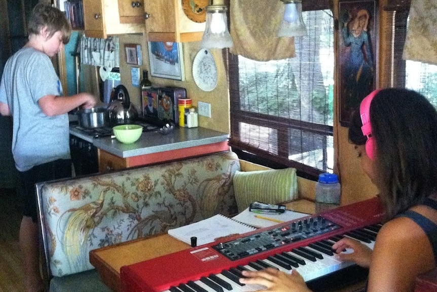 Graciana plays the keyboard a the bus dining table while Banjo prepares food in the adjoining kitchen.