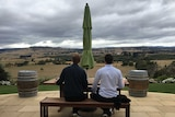 Two people sit on bench with a glass of wine looking out over a rolling paddock