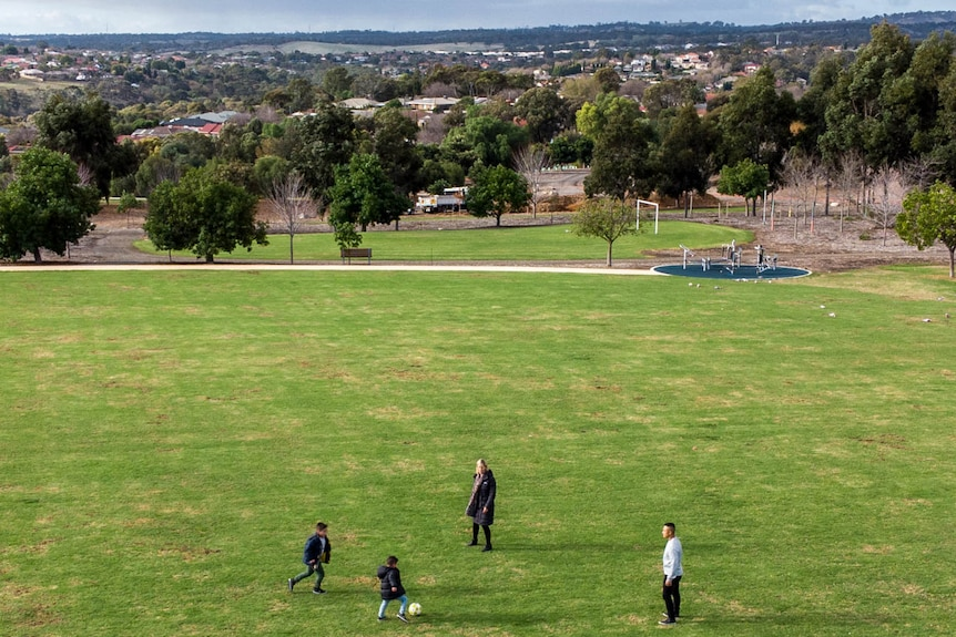 A drone shot shows a young family kicking a soccer ball on a lush green field