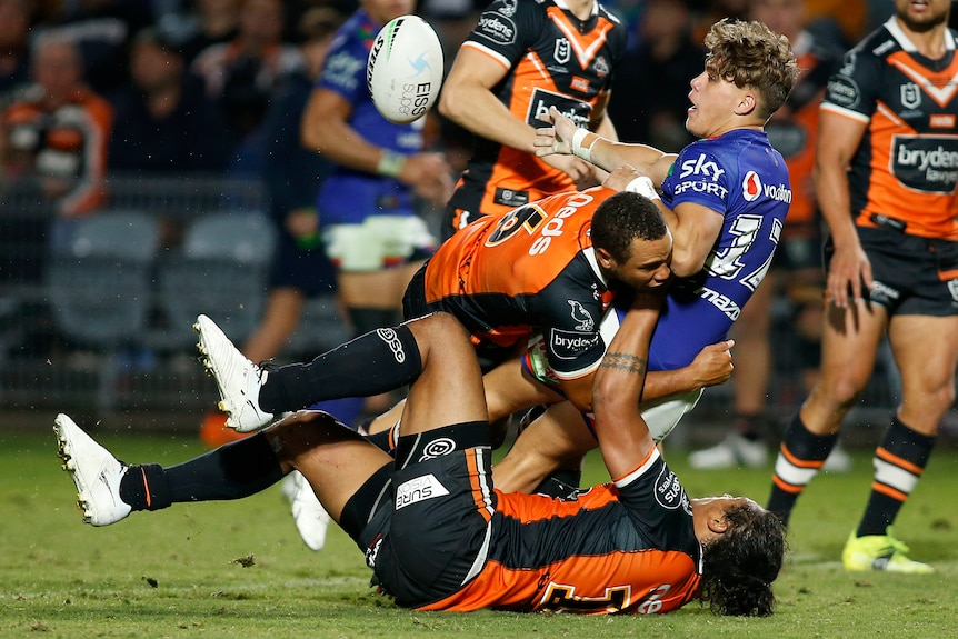 A Warriors NRL player offloads a pass while being tackled by two Wests Tigers' opponents.
