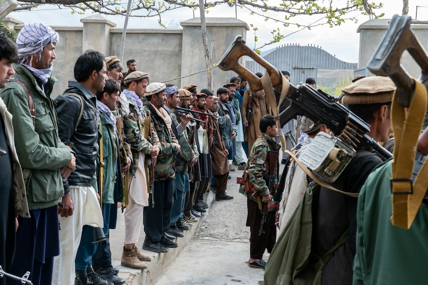 Men line up with guns over their shoulders and long robes listening to someone talk