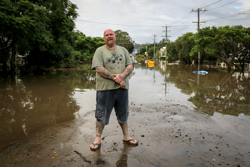 A man standing in front of flood waters in Lismore.
