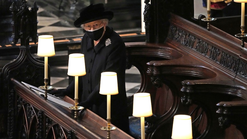 Wearing all black and a face mask, the Queen stands alone in the pews