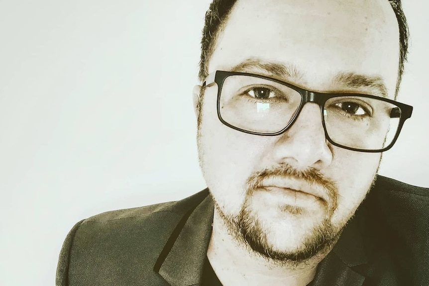A man with a goatee and prescription glasses weara a v-neck t-shirt and a blazer in a black-and-white selfie.