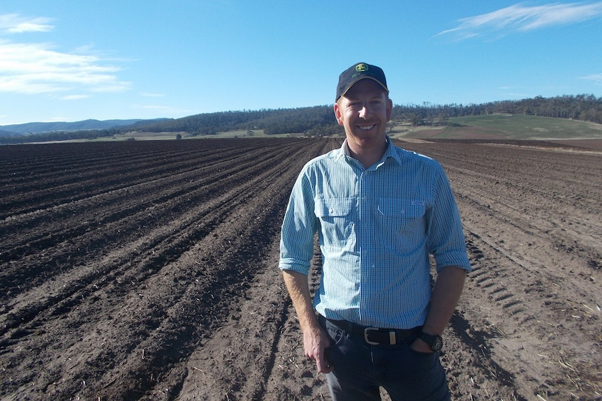A man in a blue shirt and cap stands in a ploughed field with his hands in his pockets.