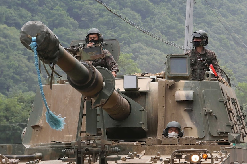 South Korean army soldiers ride a howitzer tank during a training exercise near the border with North Korea.