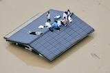 People wait to be rescued on the top of a house in Kurashiki.