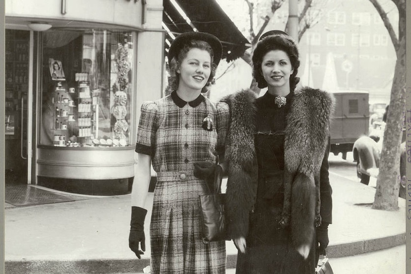 Two models cross the street near Gregory's shop in the year 1941.