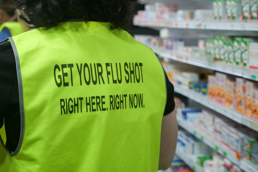 A person wearing a high vest saying 'get your flu shot right here, right now'.